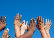 Image of outstreched hands, of different skin colour, against a blue sky
