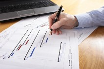 Image of a Gantt chart with hand holding pen making amendments to it